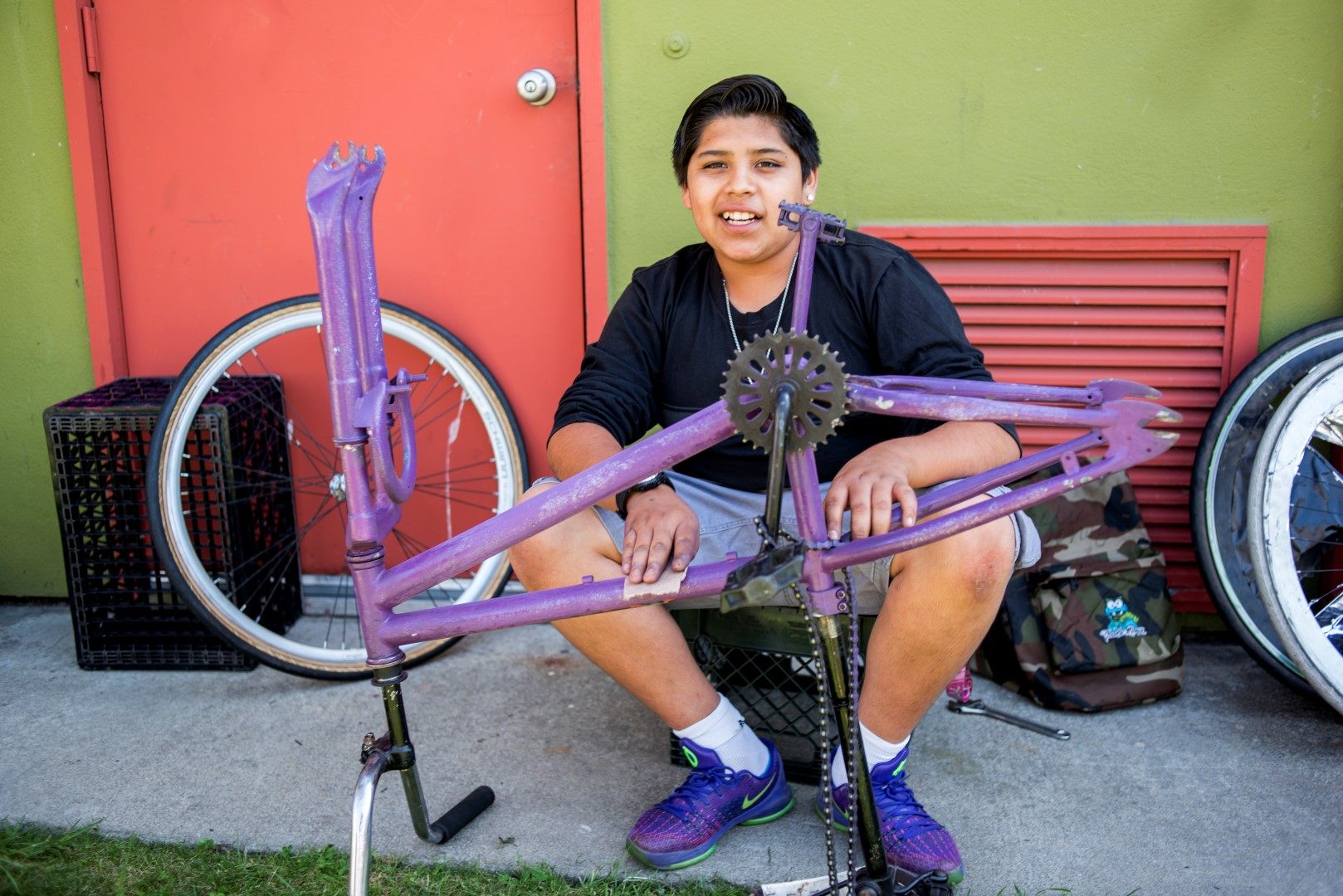 Image: a boy works on his bike. Photo: Pamela Palma Photography