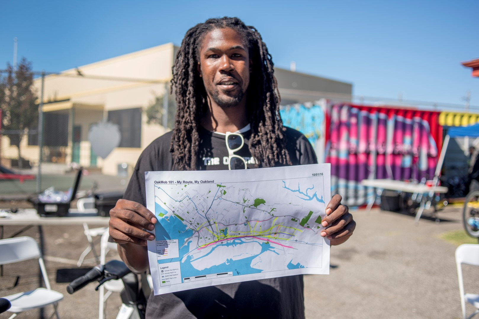 Image: a man holds his My Route My Oakland map. Photo: Pamela Palma Photgraphy