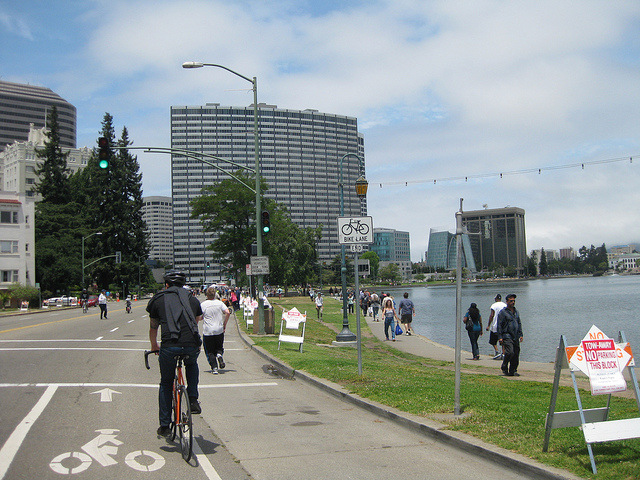 People walk and bike along Lake Merritt in Oakland