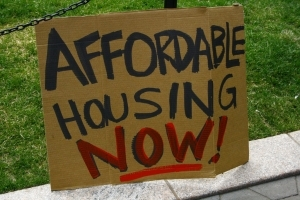 "sign saying ""affordable housing now"""
