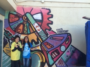 two middle school students spray paint a mural