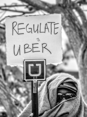 "Anonymous Uber driver with face covered and a protest sign that says ""regulate uber"""