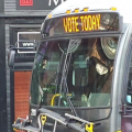 "bus with ""vote today"" on its display banner"