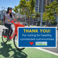 woman on bike share with the words, thank you for voting for healthy, connected communities