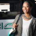 Picture of person smiling in front of an AC Transit bus.