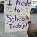 "A student signs his name on the ""I Rode to School Today"" sign at Rancho los Positas Elementary School."