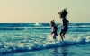 Image: two girls play in the ocean. Photo: Adobe Stock